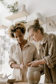 Two women making a sculpture.